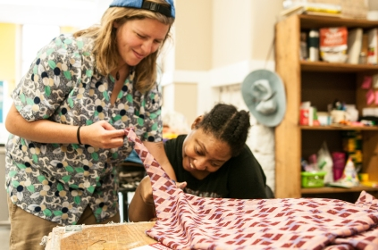 Kachelle and Alicia work on a woven rug project, using used and recycled materials
